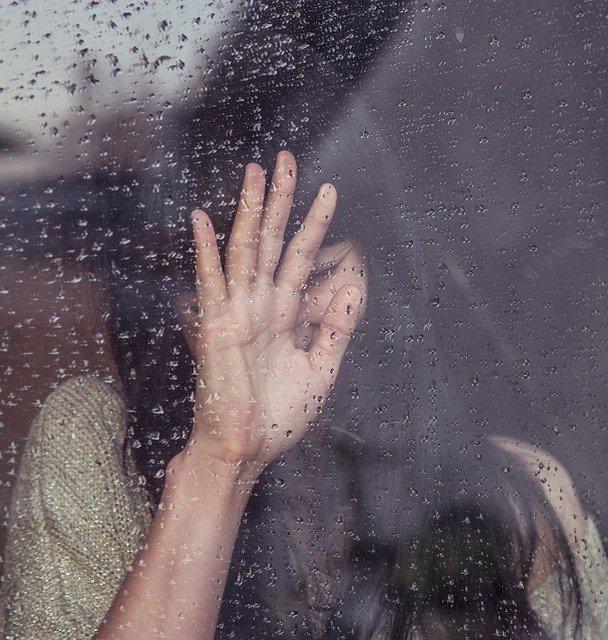 Femme triste derrière une fenêtre