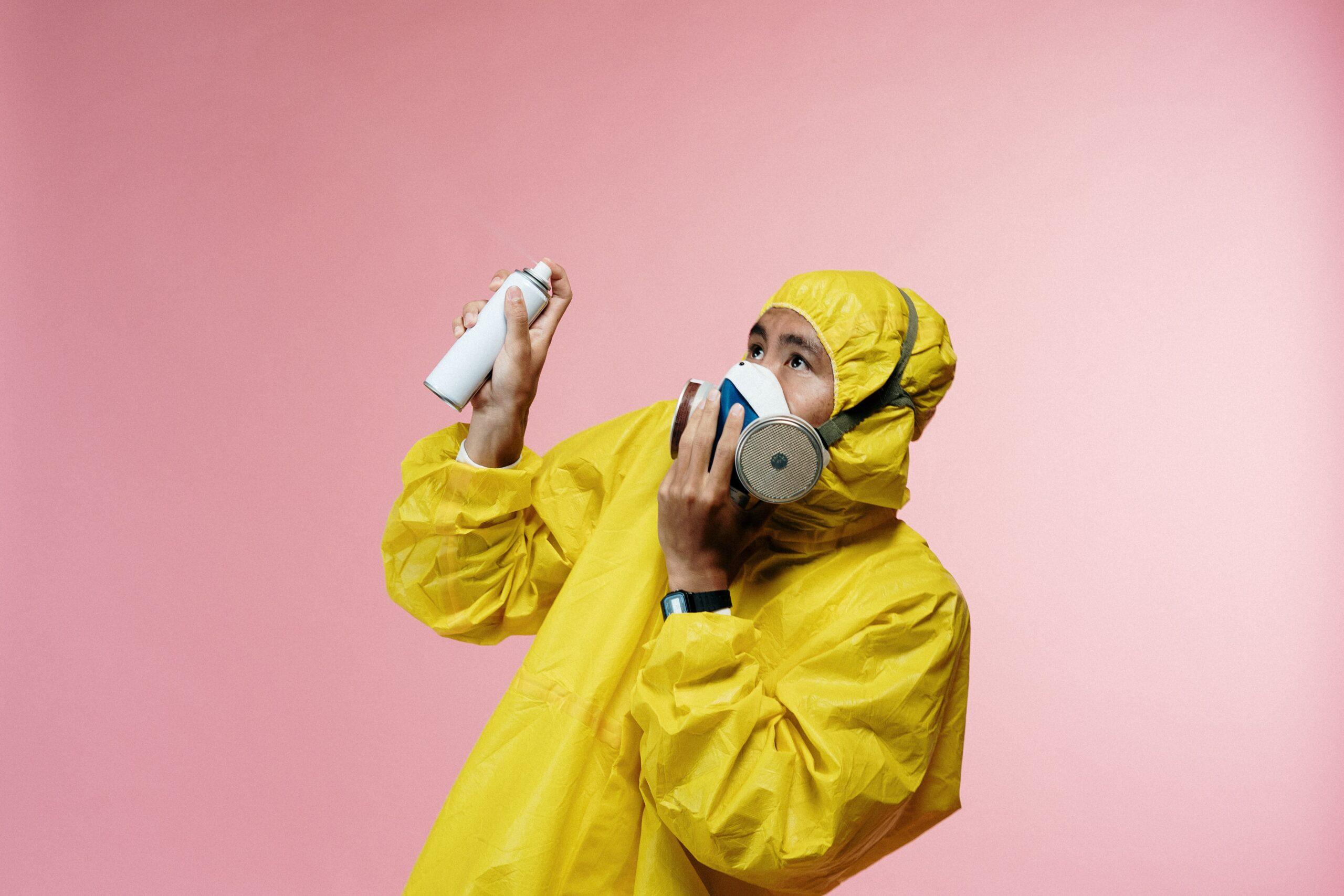 Homme en combinaison et masque avec un spray
