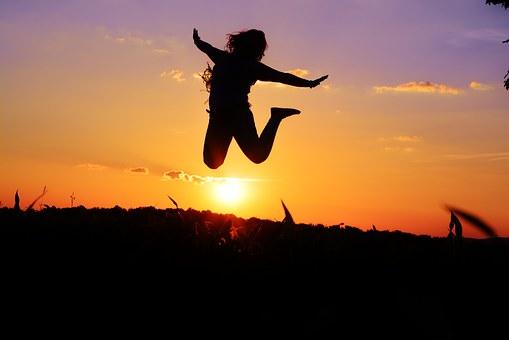 vivre.femme qui saute de joie au coucher du soleil