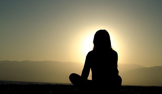 Femme assise face à la montagne