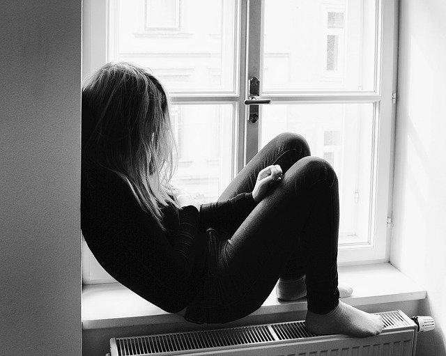 Adolescente assise sur le bord d'une fenetre triste