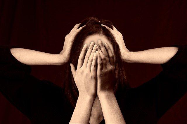 Femme visage caché par ses mains
