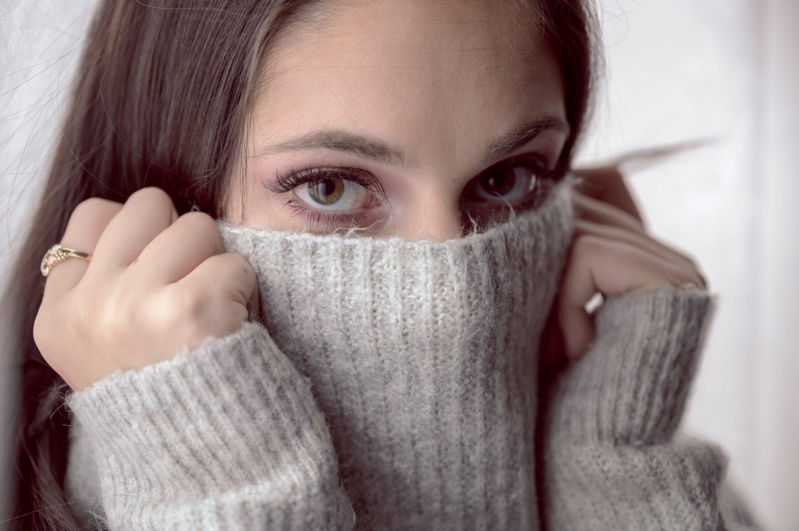 Complexée, une femme couvrant son visage avec un pull gris