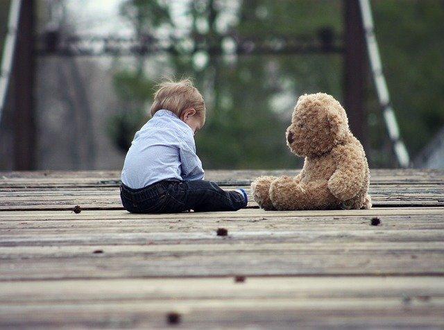 Jeune enfant assis avec son ami imaginaire un ours en peluche