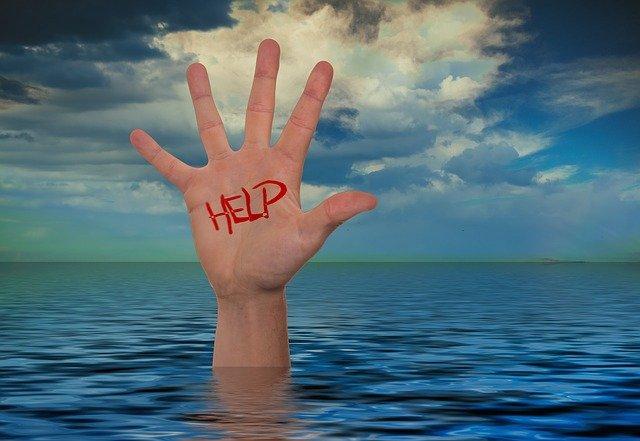 Perdre pied : Main qui sort de l'eau avec écrit Help